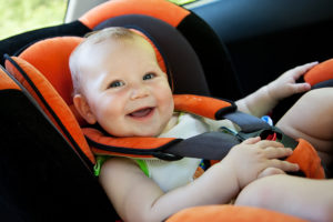 bigstock-baby-girl-smile-in-car-27329060