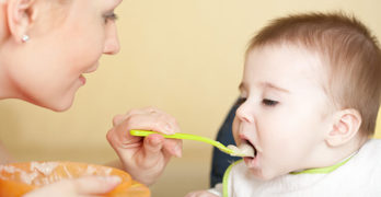 Beikost: Baby wird mit Brei gefüttert